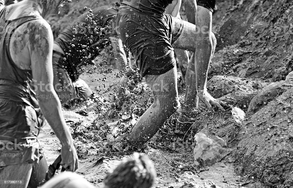 mud runners crossing the obstacle stock photo
