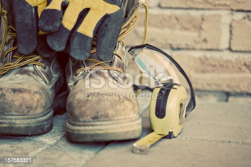Construction boots and gloves. Desaturated grunge look applied.