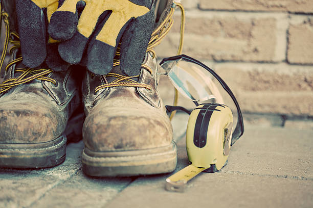 Muddy construction work boots with gloves and tape measure Construction boots and gloves. Desaturated grunge look applied. boot stock pictures, royalty-free photos & images