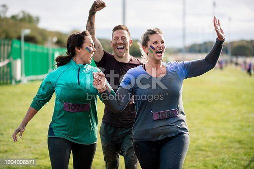 Ecstatic friends cheerfully approaching end of Stampede run, achievement, fun, carefree