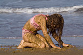 A young girl covered in mud at the beach