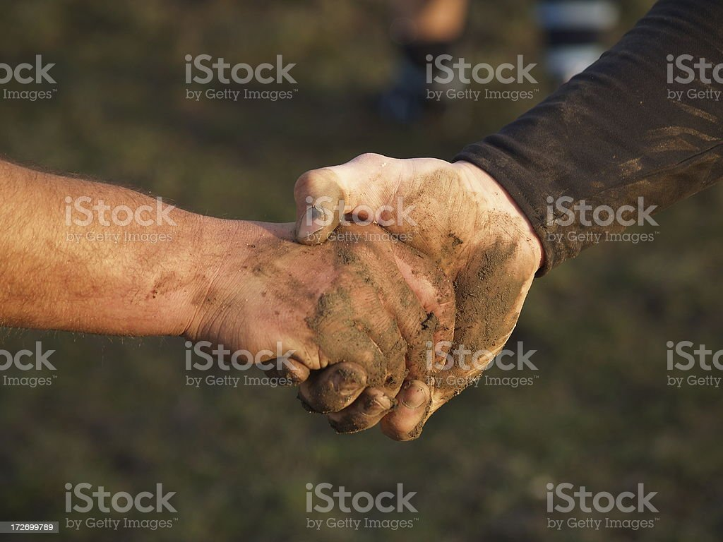 Muddy hand shake stock photo