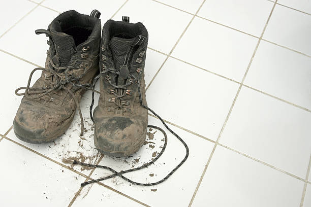 muddy hiking boots leaving dirt on clean white tiles - dirty shoes stock photos and pictures