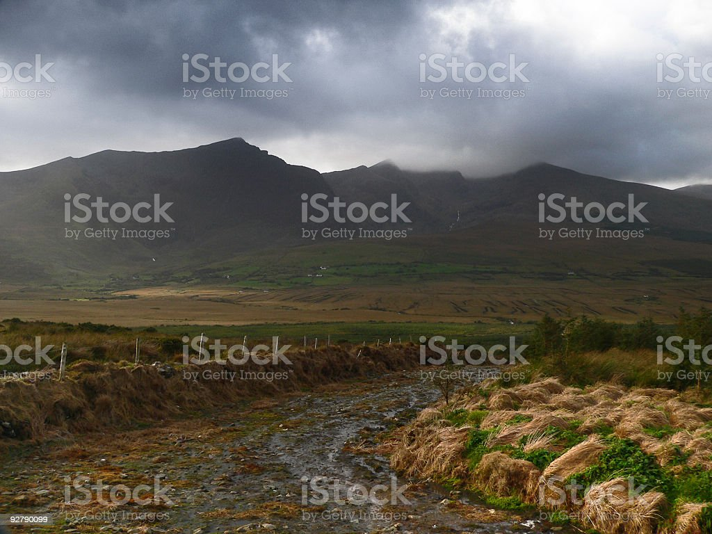 Muddy Irish country Road with bog and mountain backdrop royalty-free stock photo