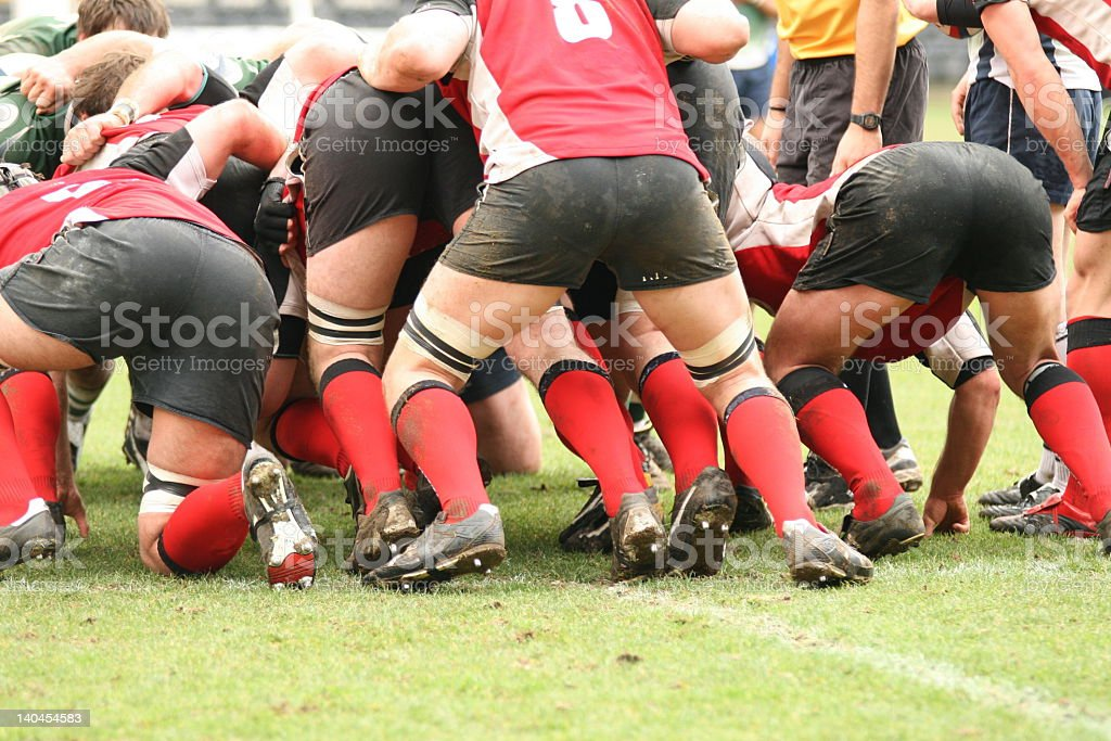 Muddy male rugby players tackling each other stock photo