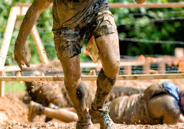muddy man running obstacle course man rising out of barbwire mud pit in obstacle course mud run stock pictures, royalty-free photos & images