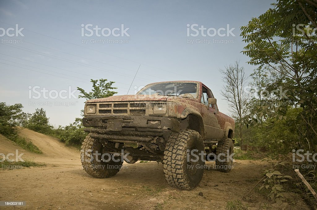 Toyota pickup truck covered with mud on dirt trails.