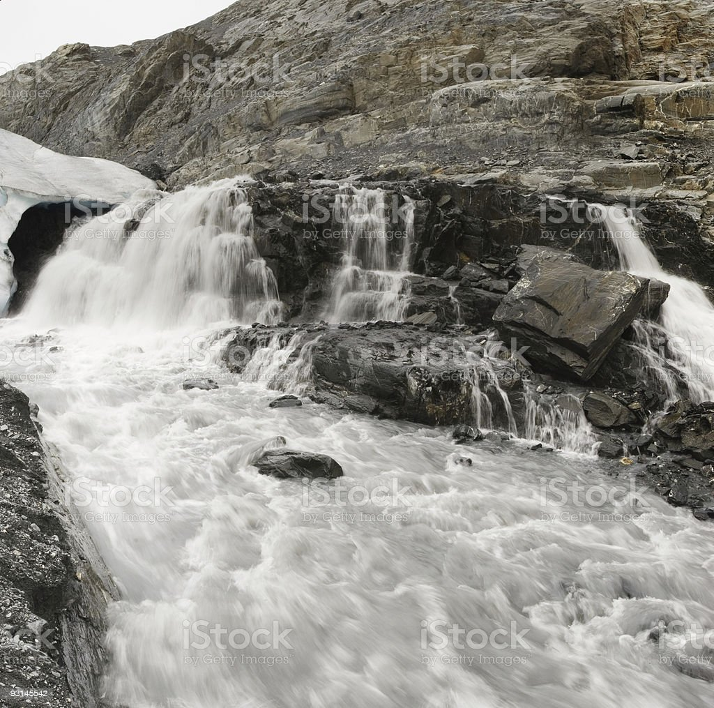 Muddy river with waterfall flowing from below the glacier royalty-free stock photo