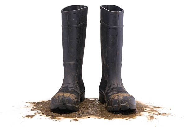 Muddy rubber boots front view stock photo
