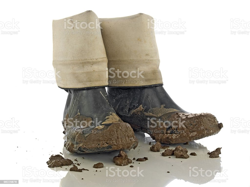 Muddy rubber working boots on white background royalty-free stock photo
