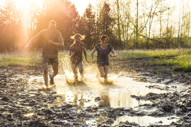 Muddy Run Three young adults are testing their agility and endurance during an extreme challenge of running through mud outdoors. Here, the sunset is behind them as they race through muddy water. mud run stock pictures, royalty-free photos & images