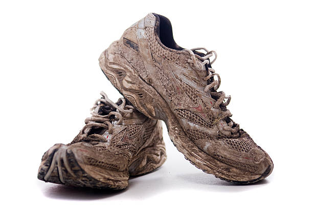 Muddy Sport shoes A pair of muddy sports shoes or trainers. mud run stock pictures, royalty-free photos & images