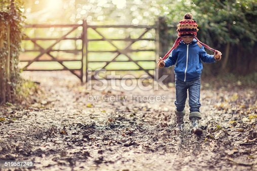 Boy walking on muddy footpath in autumn at sunset