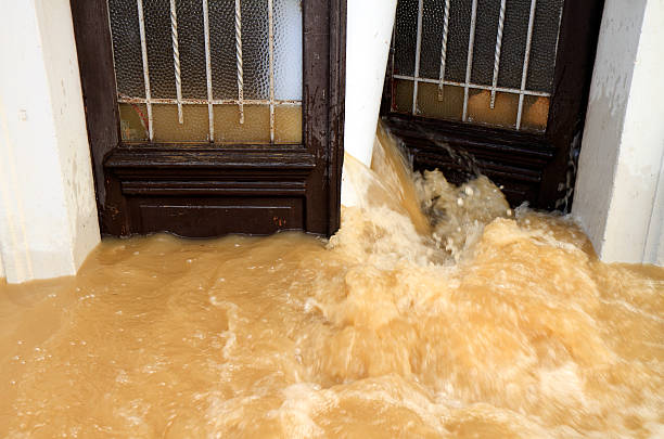 Muddy water pouring through the entrance door stock photo