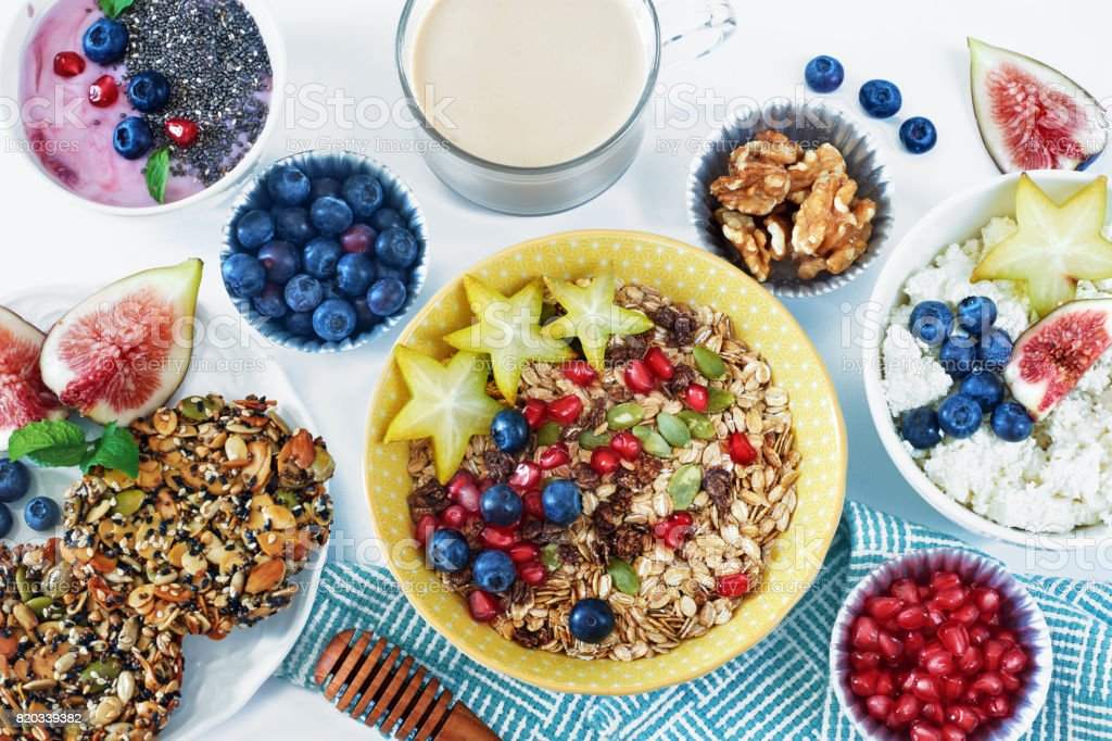 Muesli, cottage cheese, yoghurt, wholegrain cookie, fresh berry and fruit, coffee on a white table. stock photo