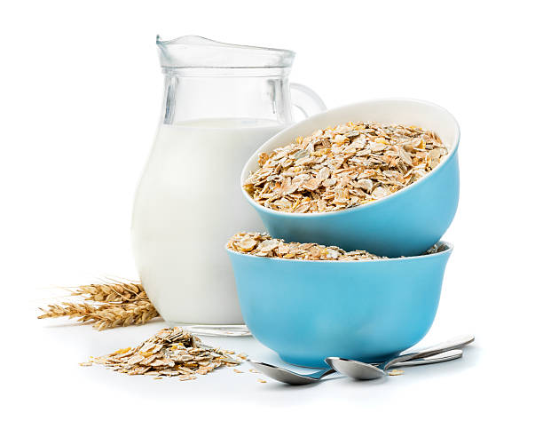 muesli in blue masks and milk jug isolated on white stock photo