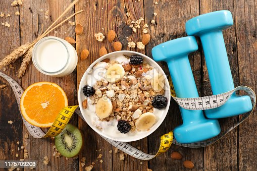 muesli with fruits and yogurt, meter and dumbbell, diet food concept