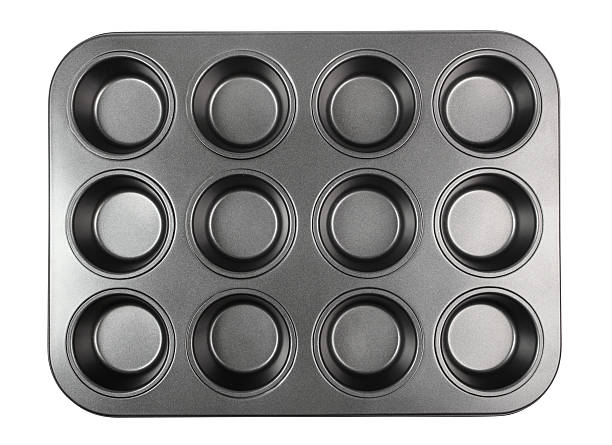 Muffin Tray Muffin Tray. Isolated with clipping path. muffin tin stock pictures, royalty-free photos & images