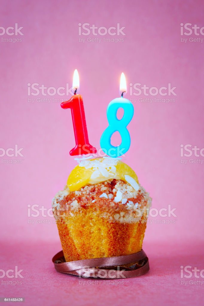 Muffin with burning birthday candles as number eighteen stock photo