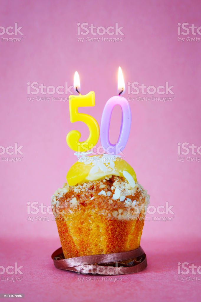 Muffin with burning birthday candles as number fifty stock photo