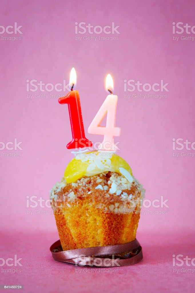 Muffin with burning birthday candles as number fourteen stock photo
