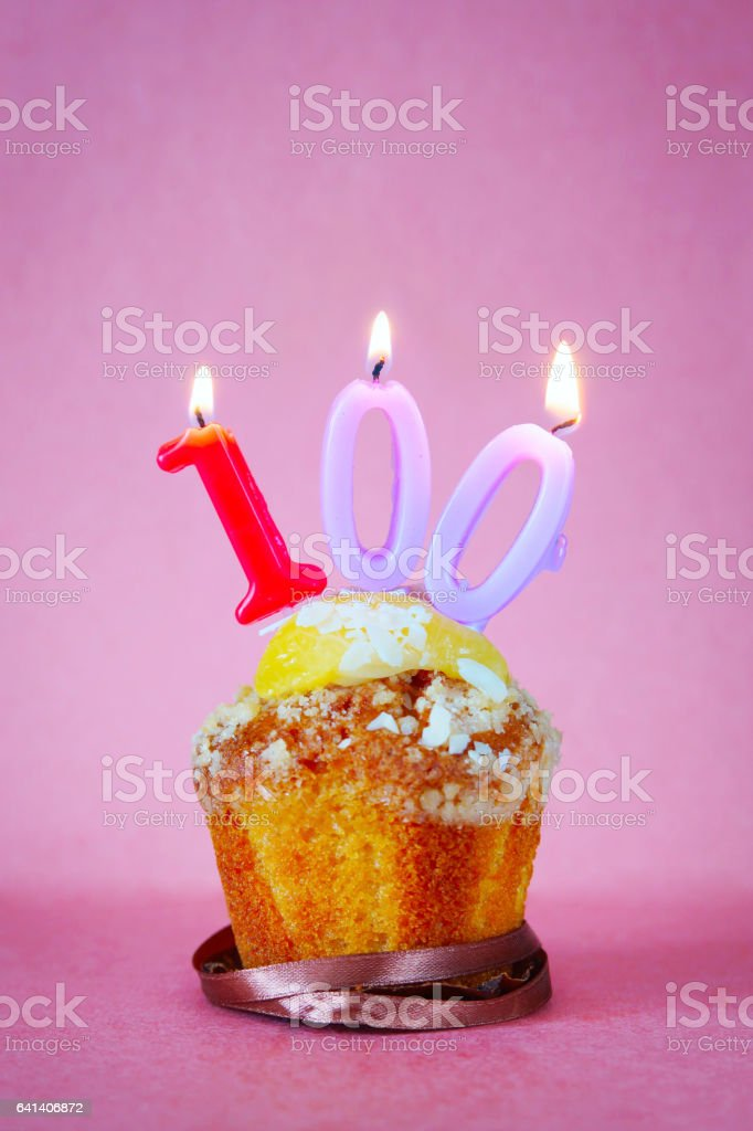 Muffin with burning birthday candles as number one hundred stock photo