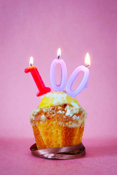 Muffin with burning birthday candles as number one hundred Muffin with burning birthday candles as number one hundred on pink background 100th anniversary stock pictures, royalty-free photos & images