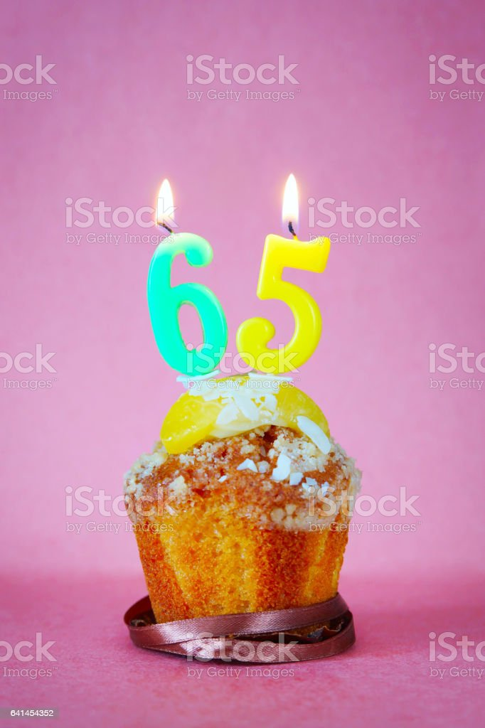 Muffin with burning birthday candles as number sixty five stock photo