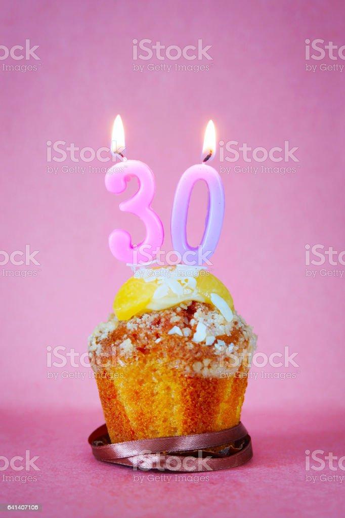 Muffins con quemando velas de cumpleaños número treinta - foto de stock
