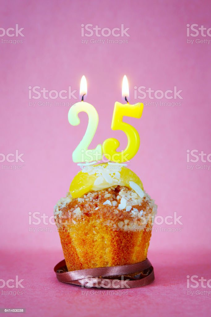 Muffin with burning birthday candles as number twenty five stock photo