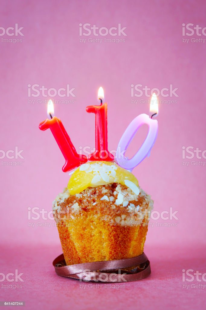 Muffin with burning candles as number one hundred and ten stock photo