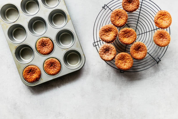 Muffins being transported from baking form to cooling rack ready to be decorated. Muffins being transported from baking form to cooling rack ready to be decorated. muffin tin stock pictures, royalty-free photos & images