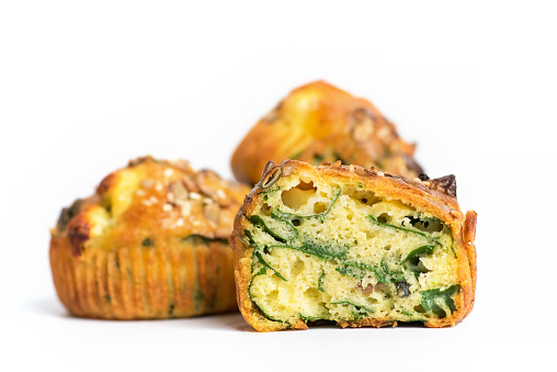 Homemade oven baked savory Muffins with eggs, spinach potatoes and cheese on white background. Healthy food concept.