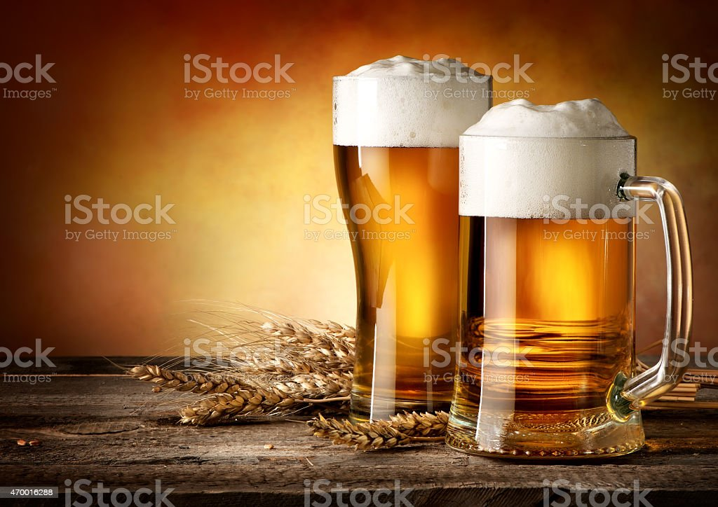 Mug and pint glass filled with beer stock photo