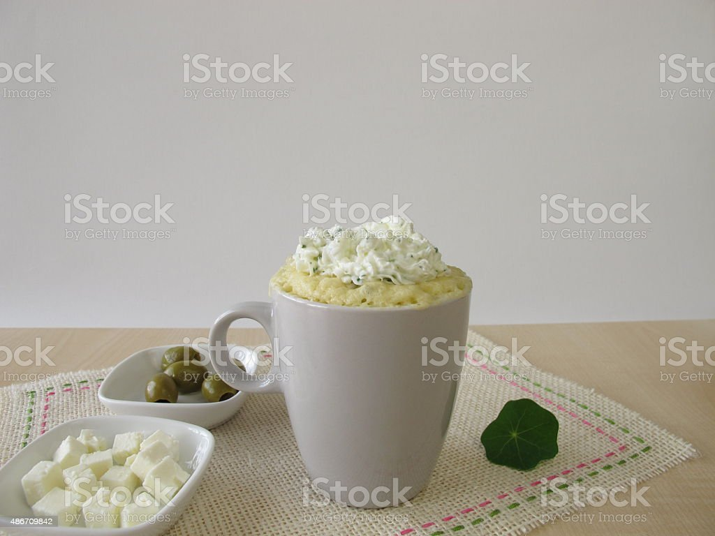 Mug cake with olives, feta cheese and herb cheese topping stock photo