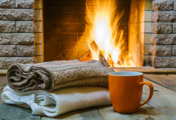 mug  for tea or coffee,  wool things near cozy fireplace. - warm house stock photos and pictures