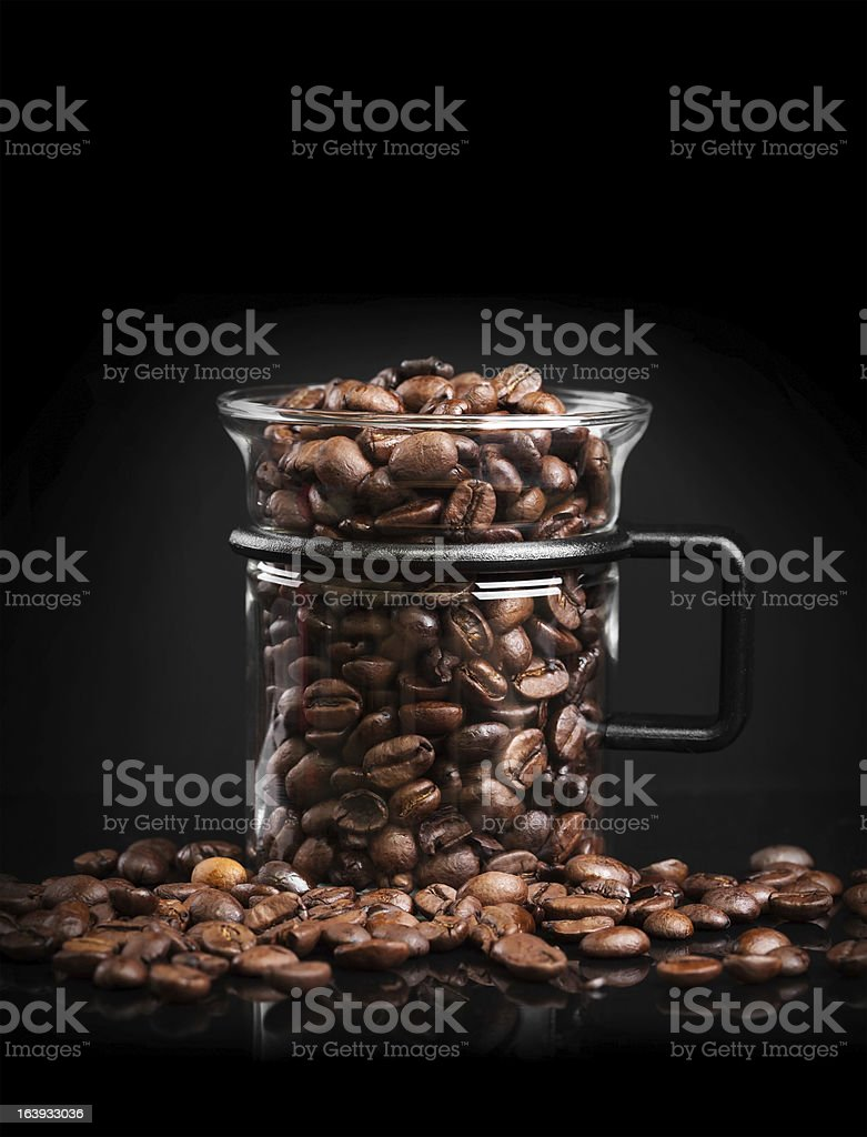 Mug made of glass with roasted coffee beans royalty-free stock photo