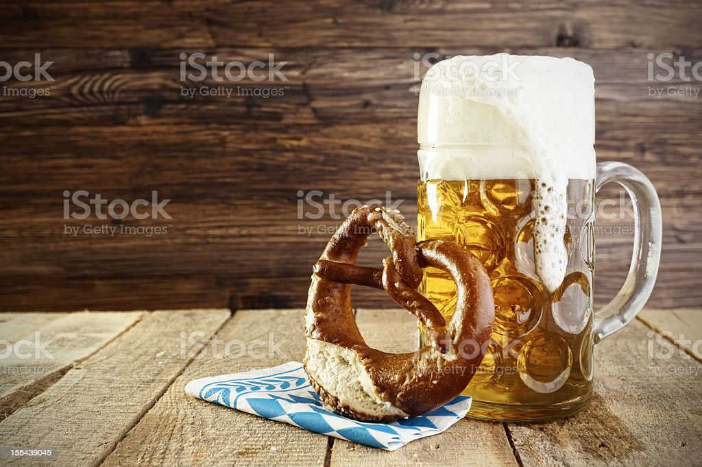 Mug of beer and a soft pretzel on a table stock photo