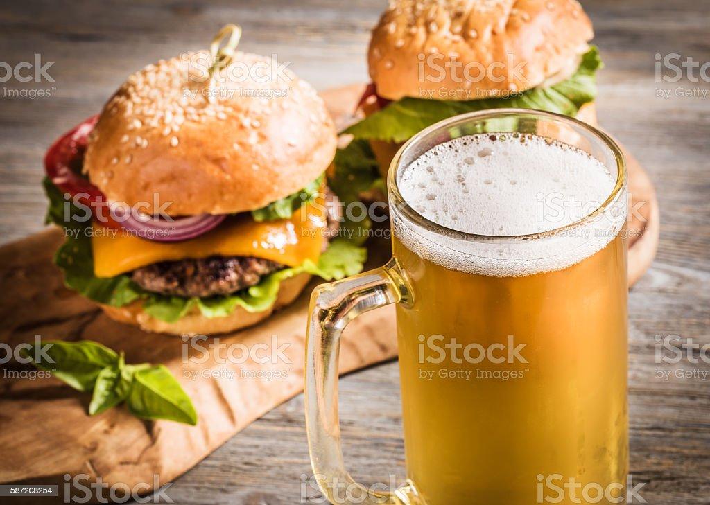 Mug of beer and hamburgers стоковое фото