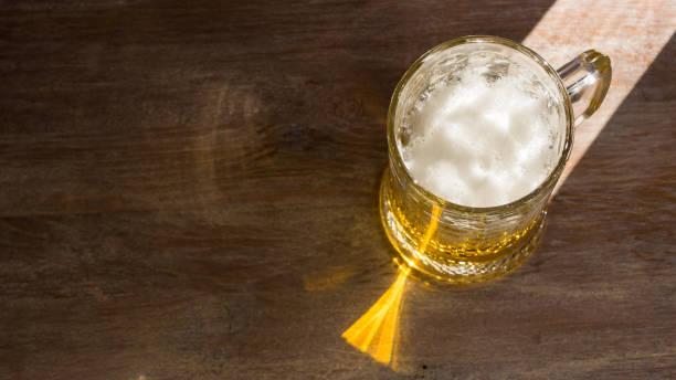 Caneca de cerveja com um tampão da espuma, iluminada pelo sol brilhante em um fundo de madeira escuro. Copie o espaço, vista superior. - foto de acervo