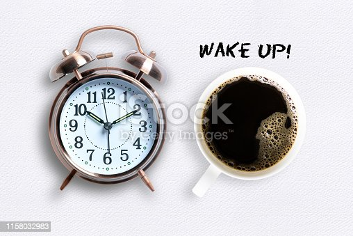 Mug of coffee and classical copper colored alarm clock with bells in a Wake Up concept on a white table with text