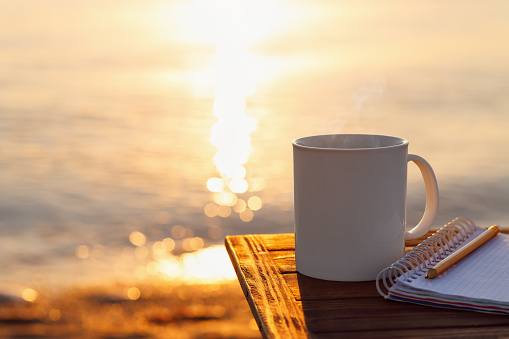 mug of coffee and notebook on table with sea at sunrise on the background