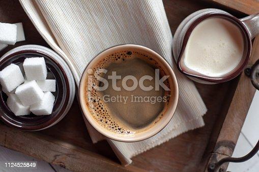 Black ceramic coffee mug with ceramic creamer and sugar bowl set on wooden serving tray.