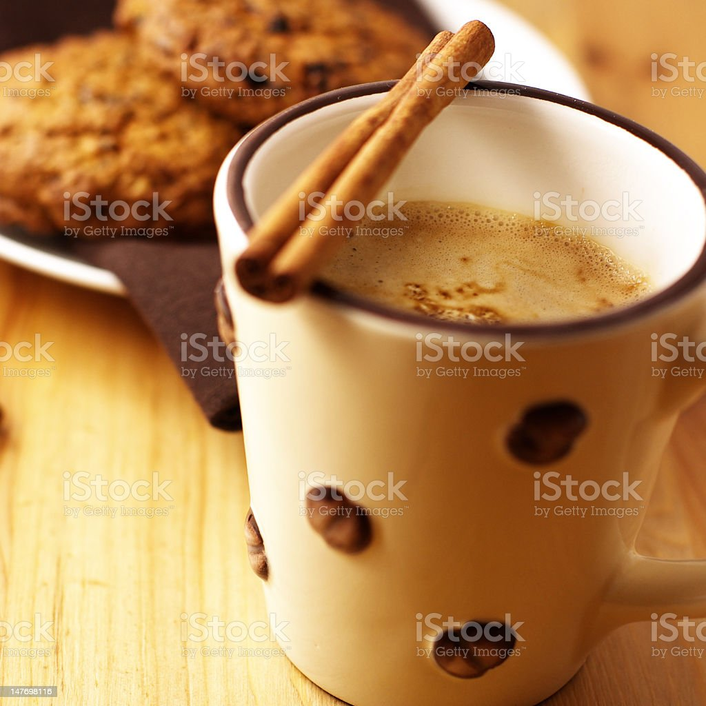 Mug of coffee with milk and a stick of cinnamon royalty-free stock photo