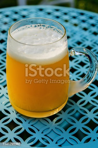 183064447 istock photo Mug of cold beer on outdoor table 1141295362