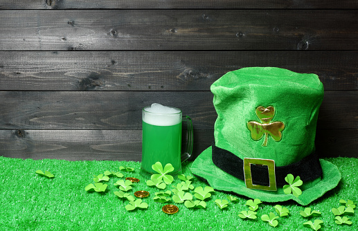 Mug of green beer and leprehaun cap, clover leaves and coins on green grass, dark wooden planks background. Saint Patricks Day banner, poster, flyer, invitation template