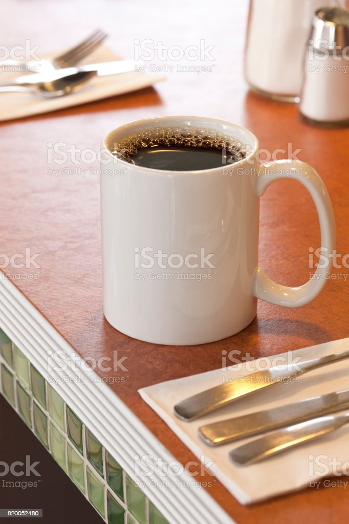 Mug of hot black coffee on counter in typical American retro style diner restaurant stock photo