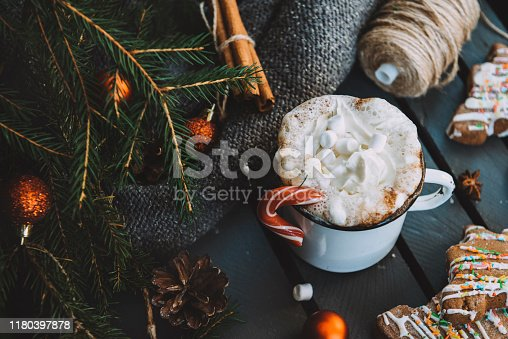 mug of hot chocolate, cocoa with marshmallows and Lollipop, fir branches, Golden balls, cookies, reel with rope on a dark background, hot winter drink