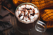 Mug of hot chocolate with marshmallows and chocolate syrup. Closeup view. Double bottom glass mug with hot chocolate beverage