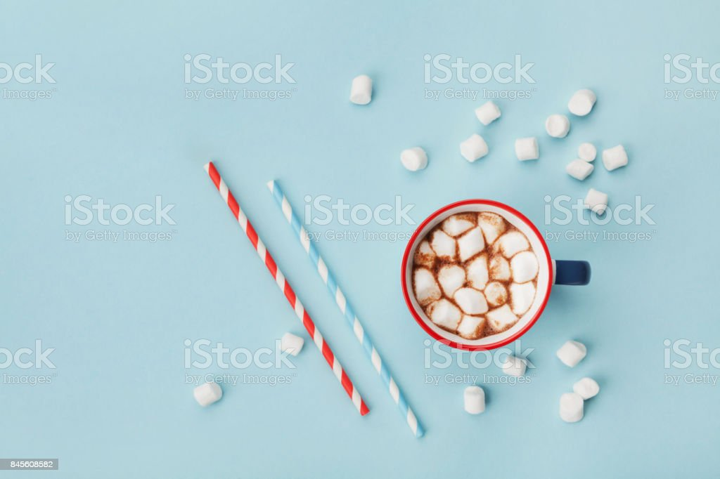 Mug of hot cocoa or chocolate and straw on turquoise table top view. Flat lay. stock photo
